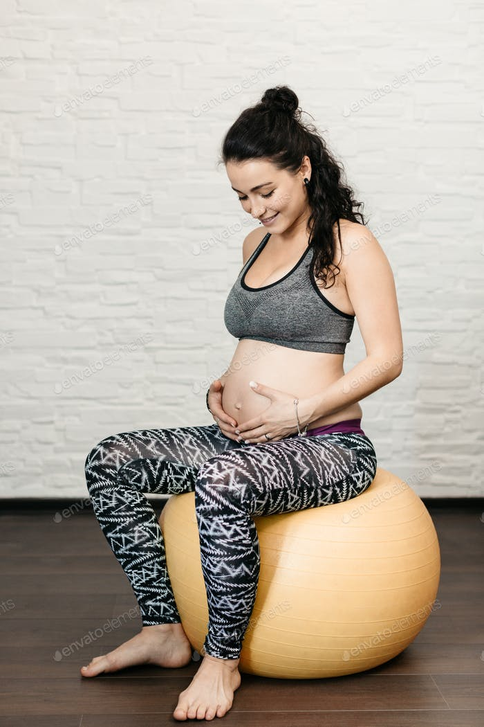 Pregnant woman sitting on a fitness ball.
