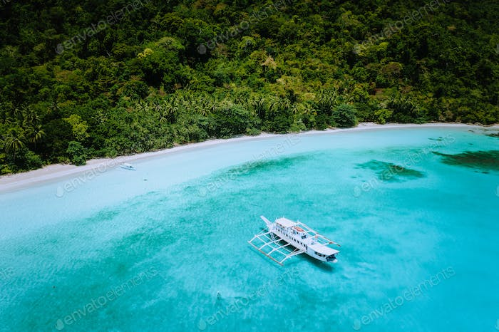 Aerial drone view of a vast scenic tropical sandy beach with lush rainforest and banca boats