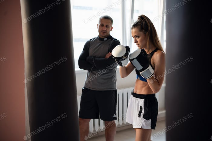 An experienced male trainer teaches a young female athlete the technique of correct hand strike