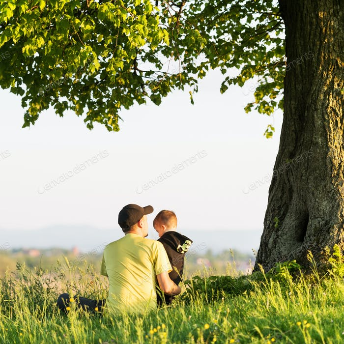 Dad with son in the spring meadow sitting under the tree