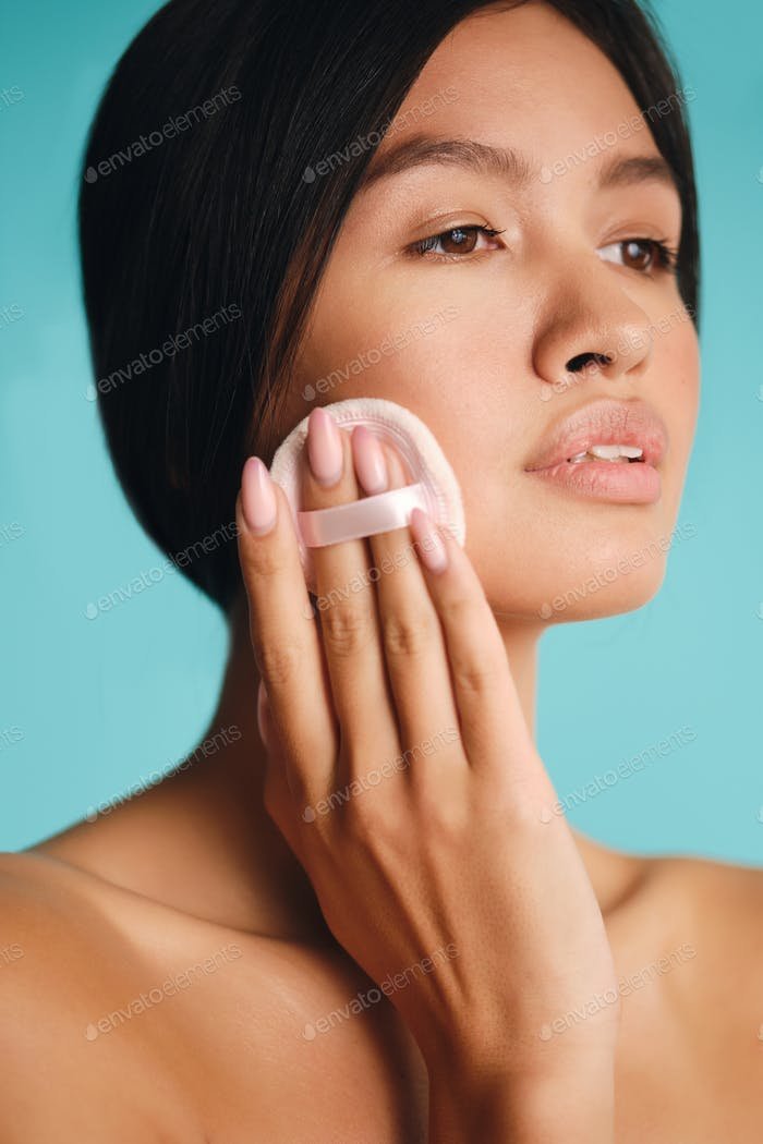 Portrait of beautiful Asian brunette girl confidently using powder puff over colorful background