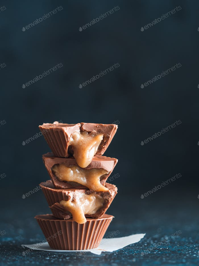 Stack of vegan chocolate cups with caramel on white