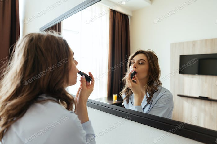 ?oncentrated young lady do makeup with lipstick