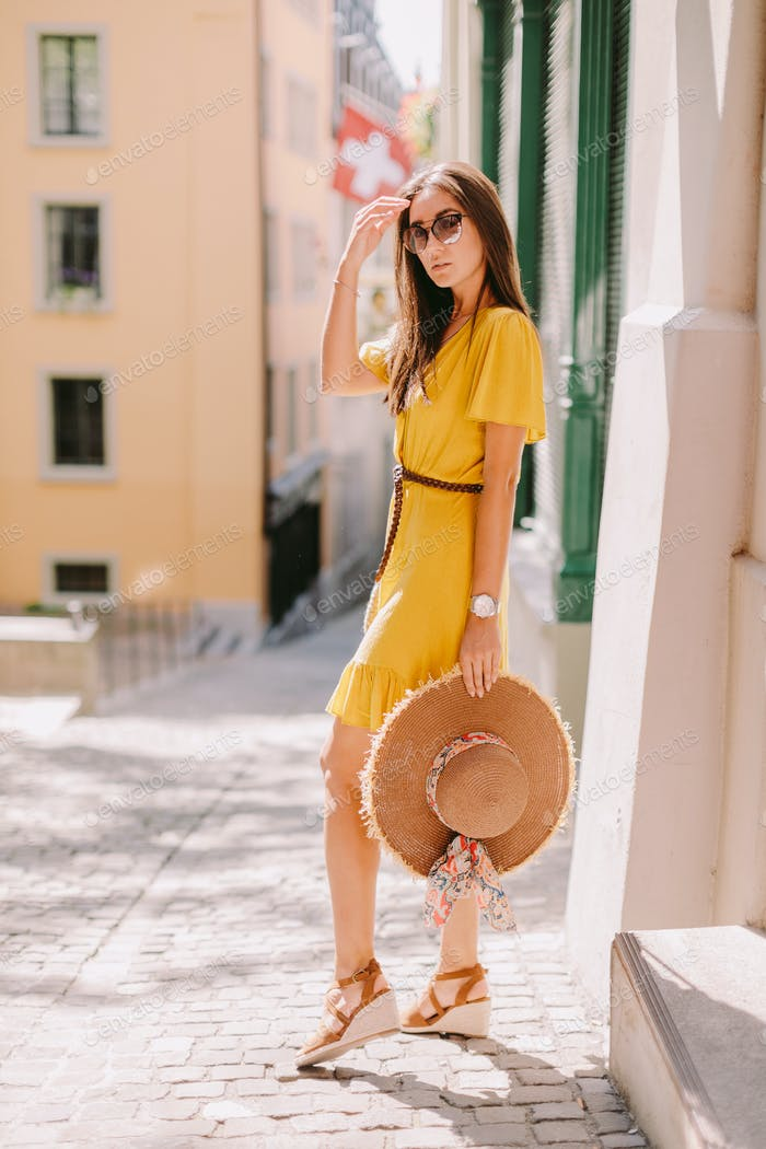 fashion woman wearing summer dress and sunglasses walk in street outdoors