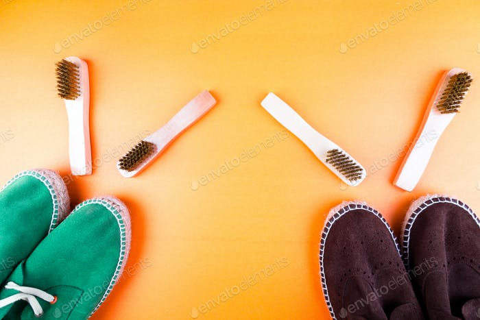 Green and brown suede espadrille shoes with brushes on yellow paper background.