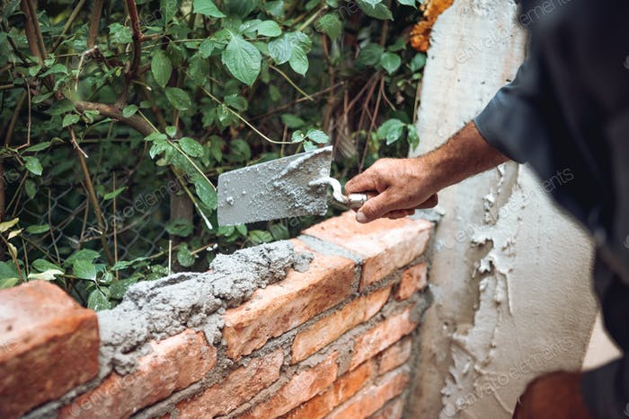 bricklayer placing and adjusting bricks with mortar.