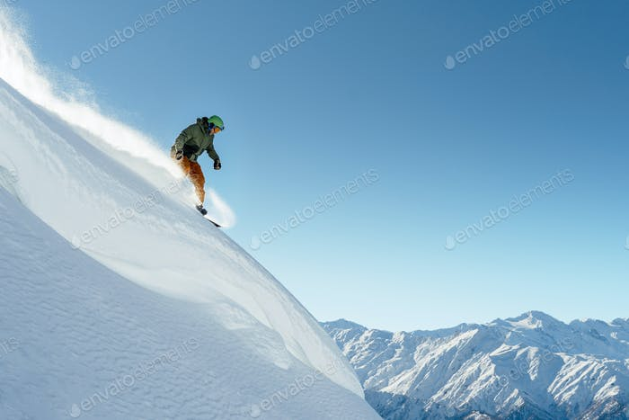snowboarder rides on steep mountainside on a beautiful landscape