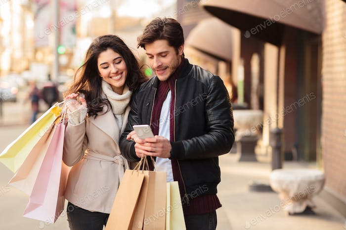 Young couple searching new boutique, using smartphone
