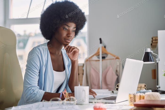 Beautiful young African woman using laptop while working in design studio