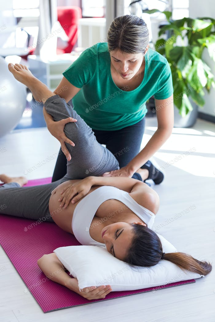 physiotherapist helping to beautiful pregnant woman for doing pilates exercises