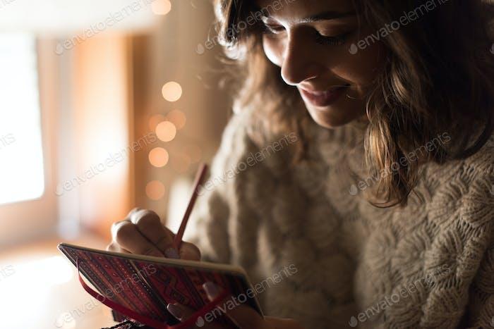 Woman writing on sketchbook