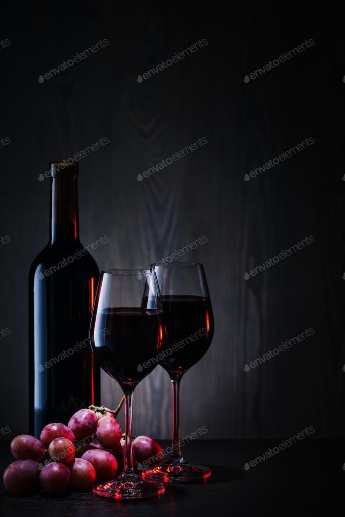 Rotwein in Gläsern und Flasche mit roten Trauben
