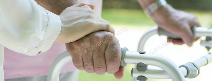 Hands holding the walking frame