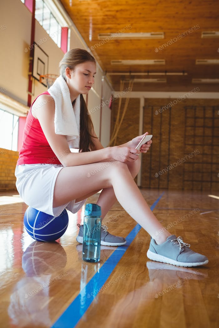 Side view of woman using phone in basketball court