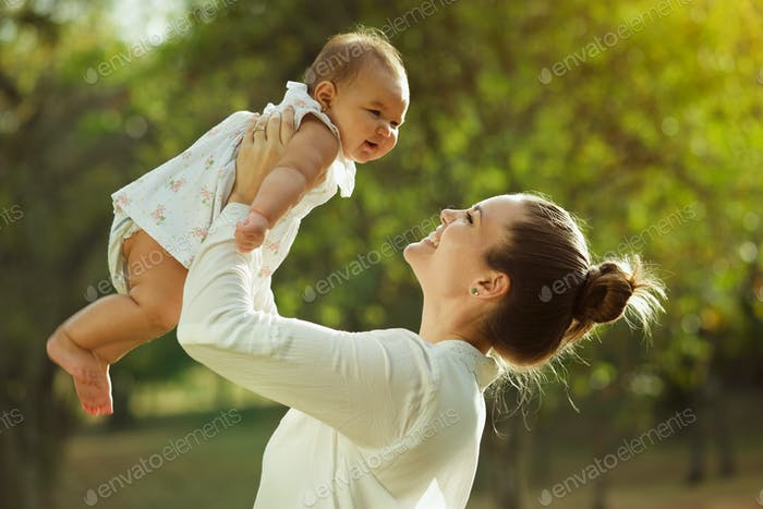 Mother Lifting Up And Turning Around Little Baby Daughter In Par