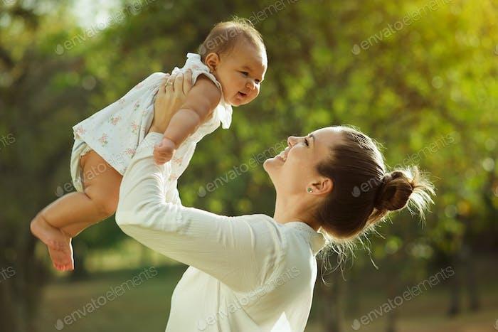 Mutter heben und drehen um kleine baby-tochter in par