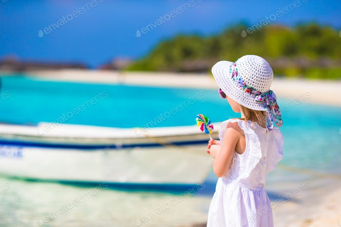 Adorable happy smiling little girl in hat on beach vacation