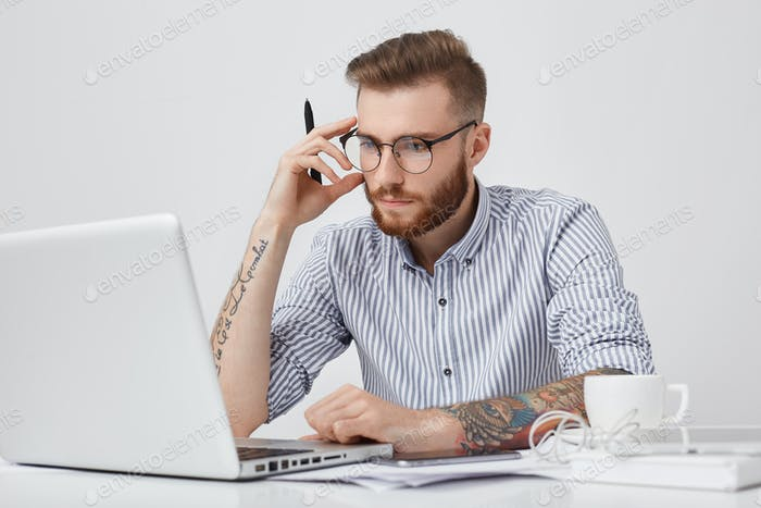 Creative male editor with tattooes, looks confidently into screen of laptop, works hard, surrounded