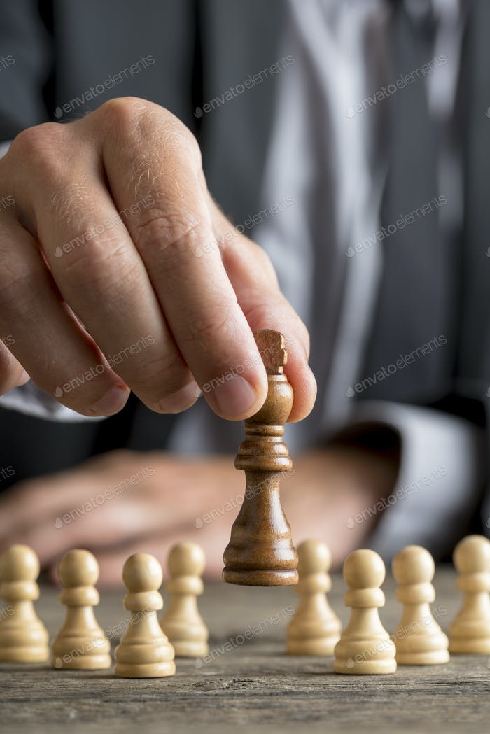 Businessman playing chess moving black king piece lifting it up