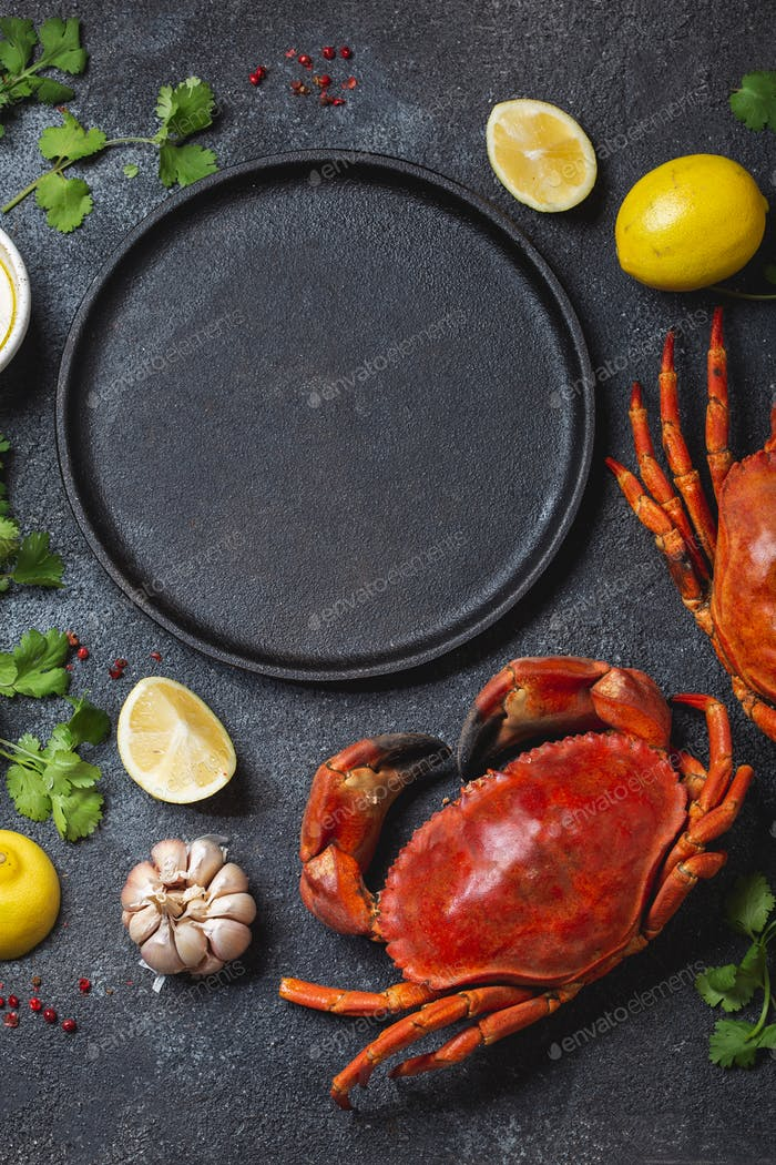 Food background with empty black plate, fresh crabs, lemons and herbs
