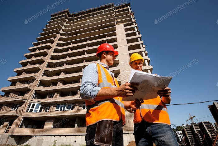 Two structural engineers dressed in shirts, orange work vests and helmets explore construction