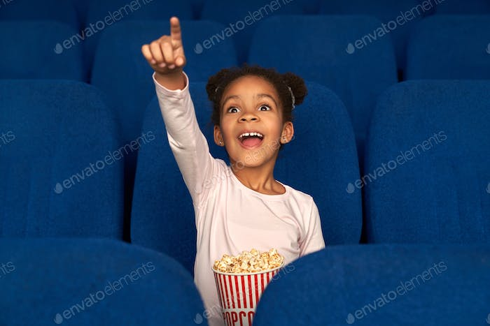 Happy girl pointing with finger at screen and watching film