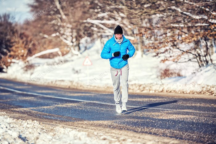 Athletic man jogging and training outdoor in park with snow on a cold day