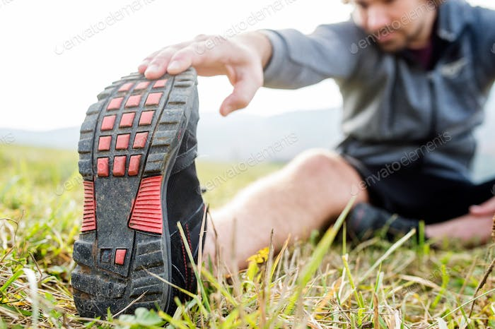 Unrecognizable young runner sitting on grass, stretching leg