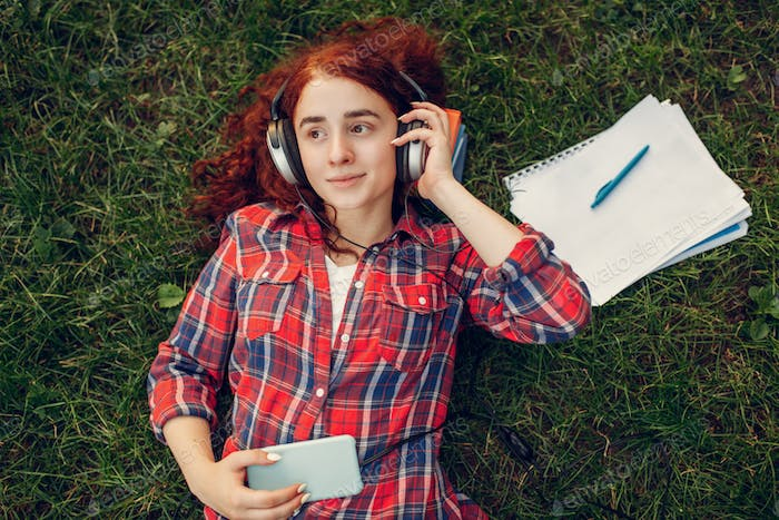 Female student in headphones lying on the grass