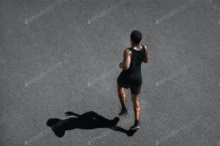 People, sports and achievement. Top shot of athletic dark-skinned runner wearing black sportswear, j
