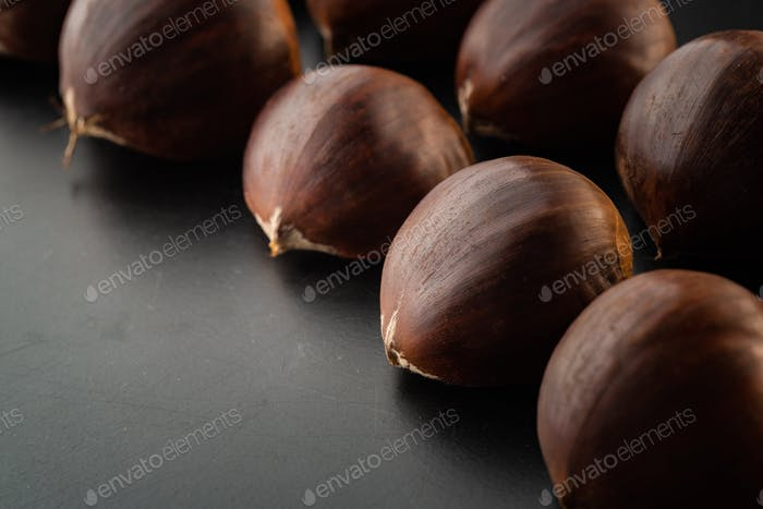 Rows of chestnuts isolated on black background