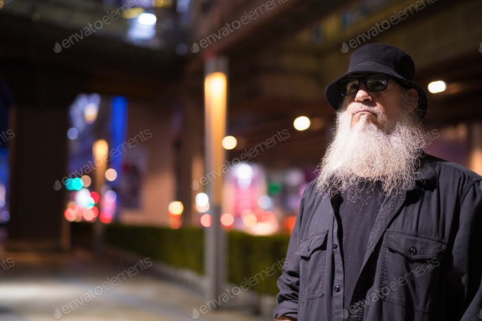 Mature bearded tourist man exploring the city streets at night