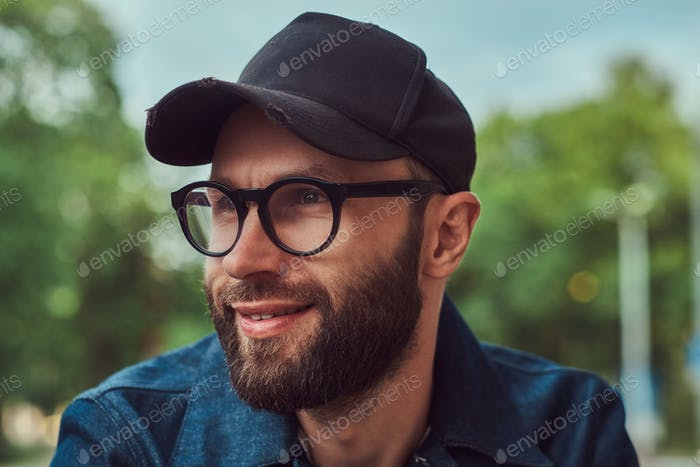 Portrait of a bearded hipster in glasses and cap outdoors.