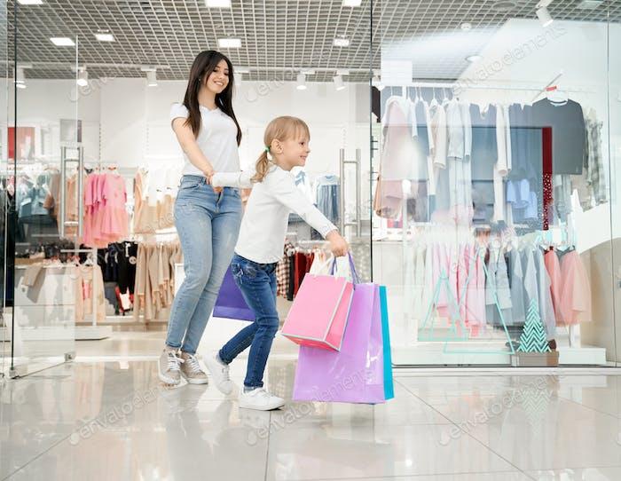 Glückliches Mädchen und Mutter spazieren im modernen Kaufhaus