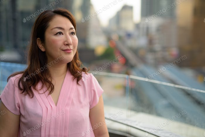 Mature Asian woman against view of the city
