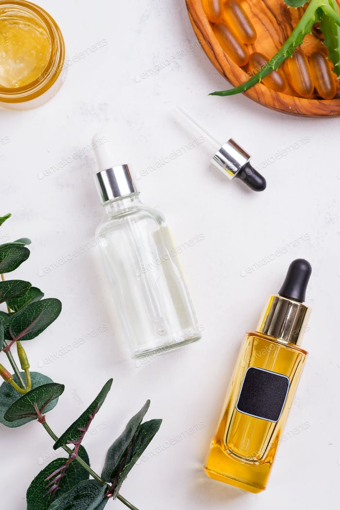 Beauty natural products with cosmetic cream, Omega-3 gel capsules, and serum in glass bottles on