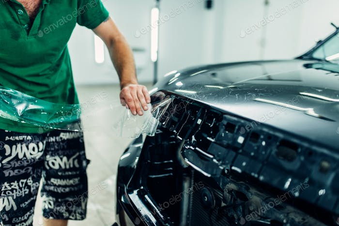 Man installs automobile paint protection film