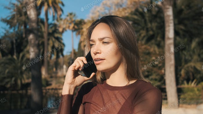 Attractive girl talking on smartphone in city park. Beautiful serious girl using phone outdoor
