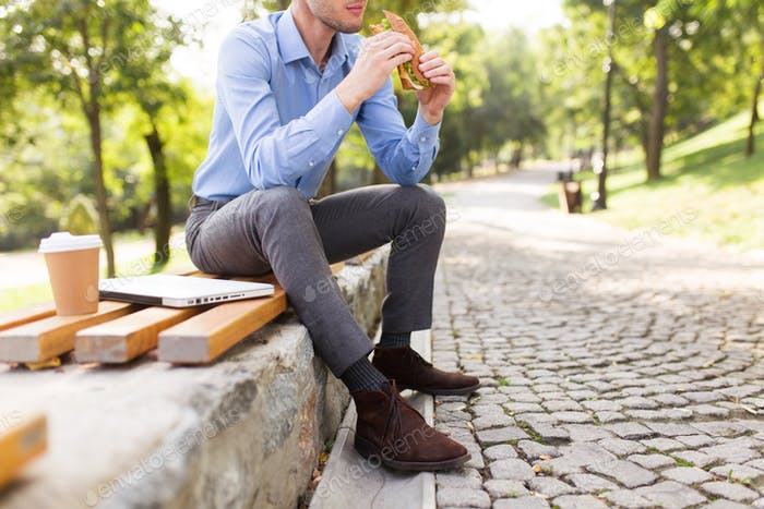 Close up man sitting on bench holding sandwich in hands with cup