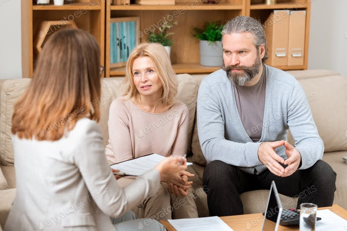 Mature man and his wife sitting on sofa and consulting with real estate agent