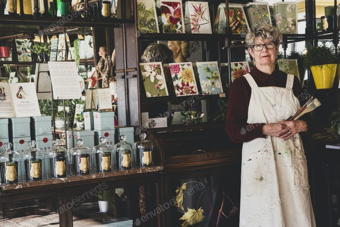 Smiling senior woman wearing glasses, red dress and white apron standing in interior design store,