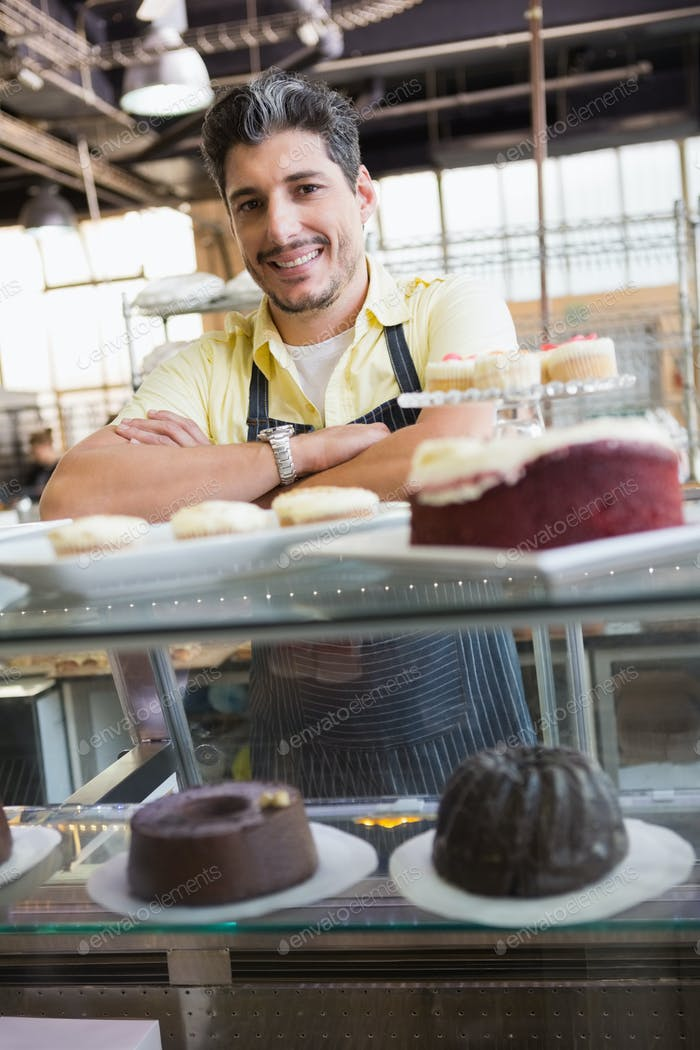 Handsome worker posing on the counter at the bakery