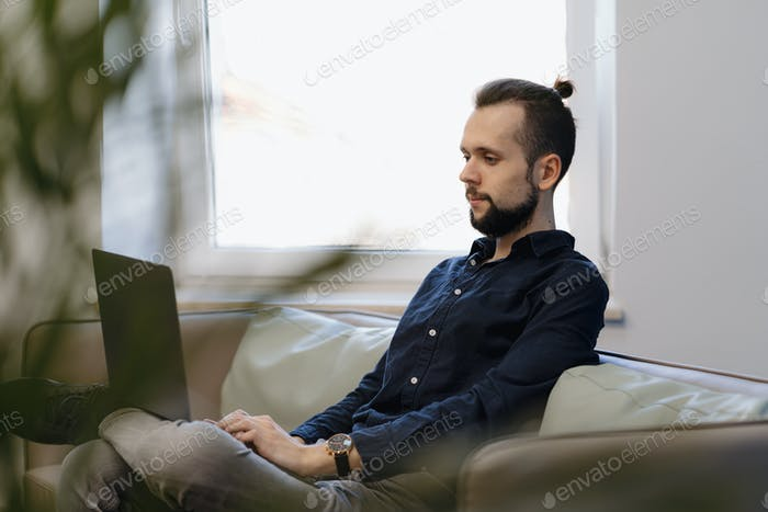 Young man working on the laptop while sitting on the sofa in the office