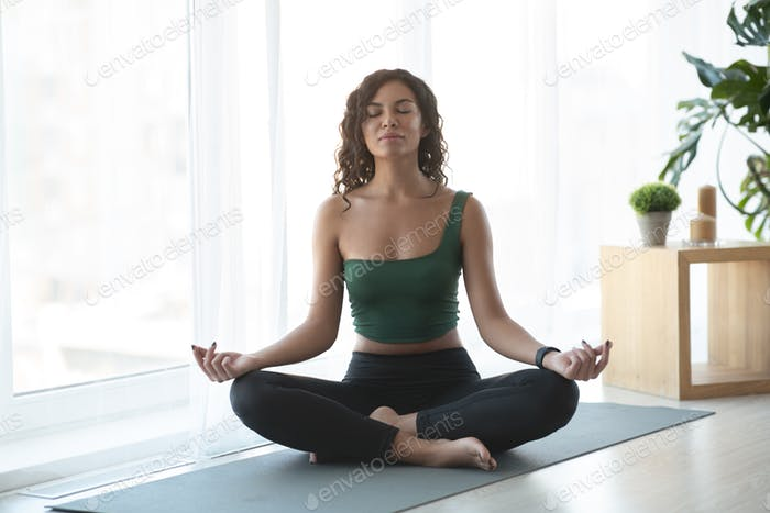 Attractive woman doing yoga and sitting in lotus position