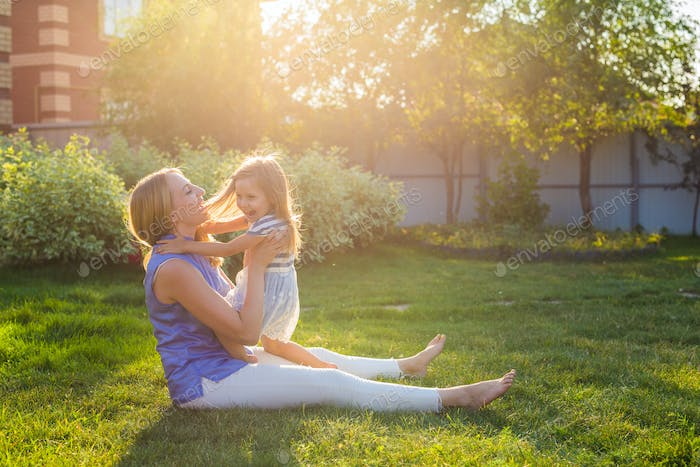 Portrait of happy loving mother and her baby daughter playing outdoors.