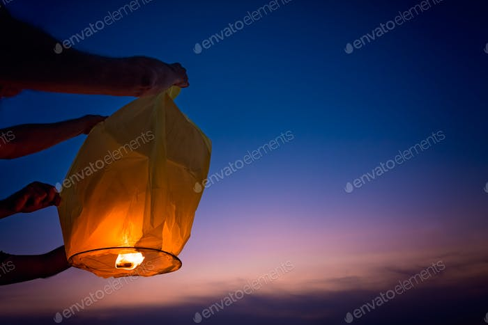 People setting off chinese lantern at sunset