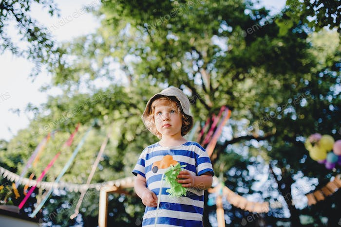 Low angle view of small boy standing outdoors on garden party, playing