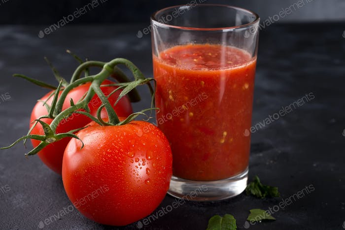 Fresh tomato juice in glass on stone background with water drops on tomatoes. Vegetable drink