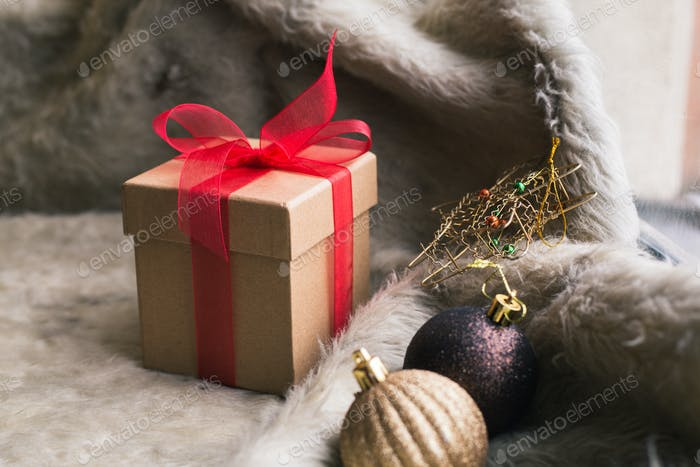 Christmas gift box with decoration on wooden background