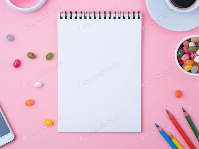 open notebook with a clean white sheet, caramel, lollipops,